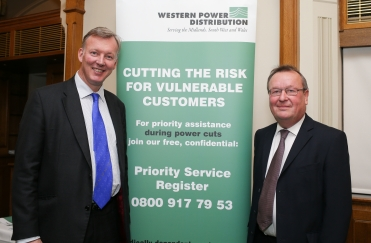 Image ©Licensed to i-Images Picture Agency. 08/12/2015. London, United Kingdom. Western Power Distribution Parliamentary Reception. Robert Symons (R) poses with Bill Wiggin MP in front of a Western Power Distribution banner about the priority assistance during power cuts. Picture by Daniel Leal-Olivas / i-Images